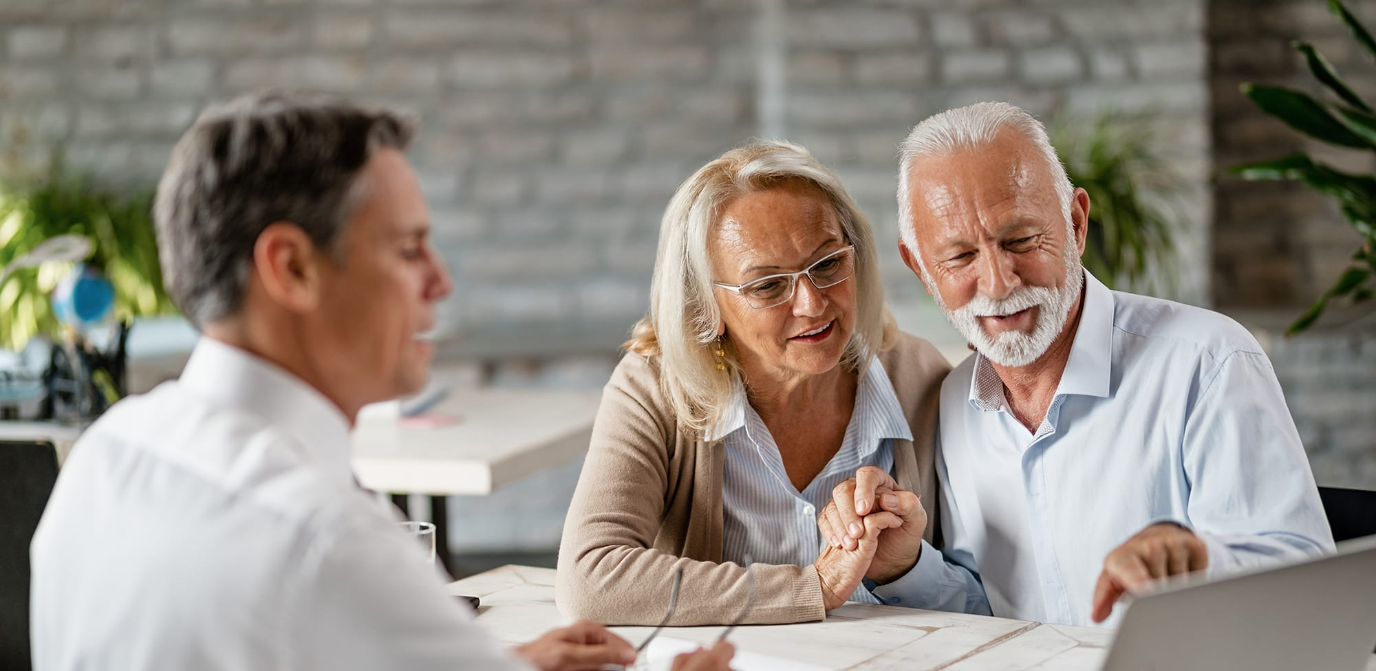 happy senior couple using computer while having a meeting with real estate agent